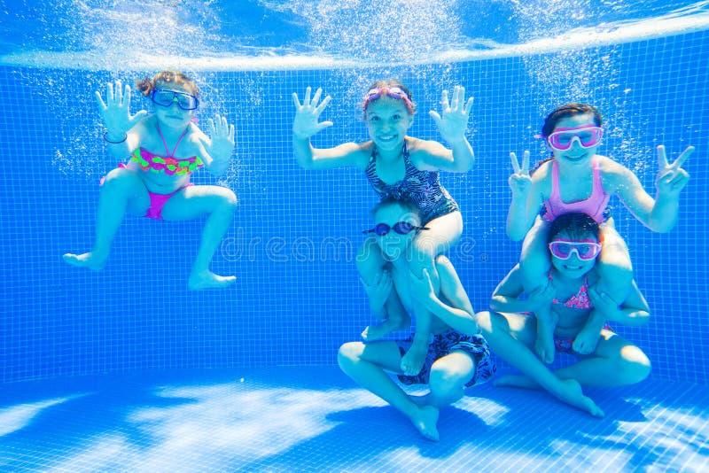 游泳在水池的小孩在水面下 库存图片