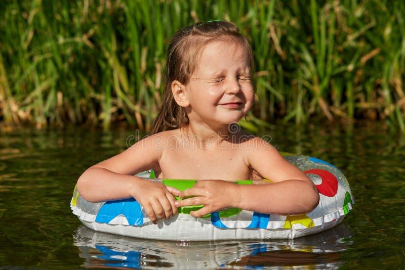 游泳在河的金发美丽的小女孩画象,学会游泳在游泳的圆环帮助下,闭上她的眼睛 库存图片