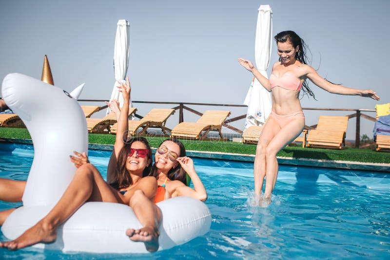 游泳在白色浮游物的两个女孩 他们cilling和有休息第三个在水中跳跃 她看得下来 另外两个 免版税图库摄影