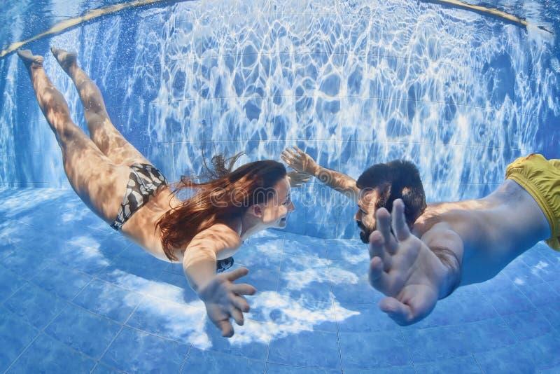 游泳在水面下在室外水池的正面夫妇 库存照片