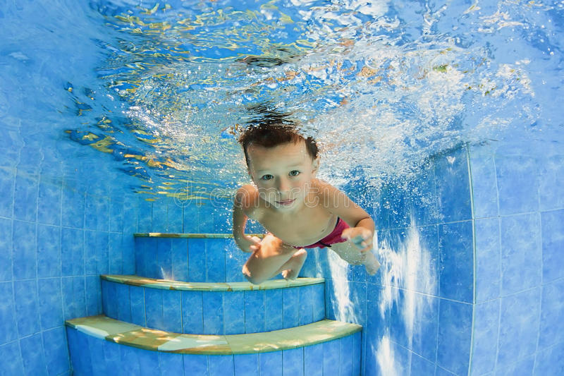 游泳在水面下在水池的小微笑的孩子 库存图片