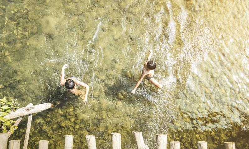 游泳在Nam歌曲河的无法认出的孩子在Vang Vieng -嬉戏的孩子真正的每天健康生活和乐趣在老挝PDR 库存照片