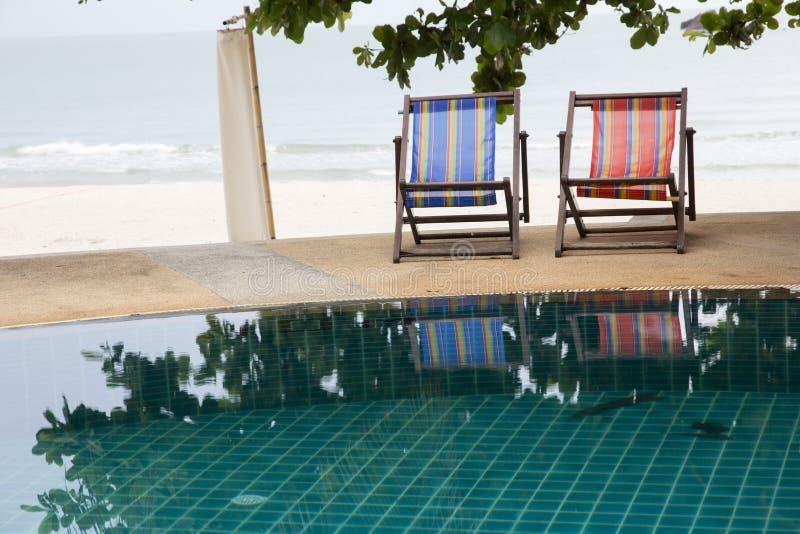 游泳场和轻便折叠躺椅在可可椰子树下在手段有美好的海视图 免版税库存图片