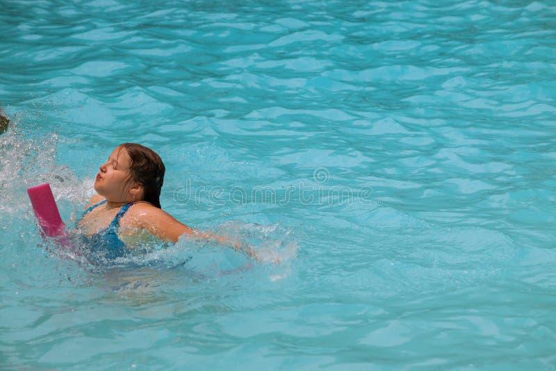 游泳场的俏丽的女孩在好日子 免版税库存照片