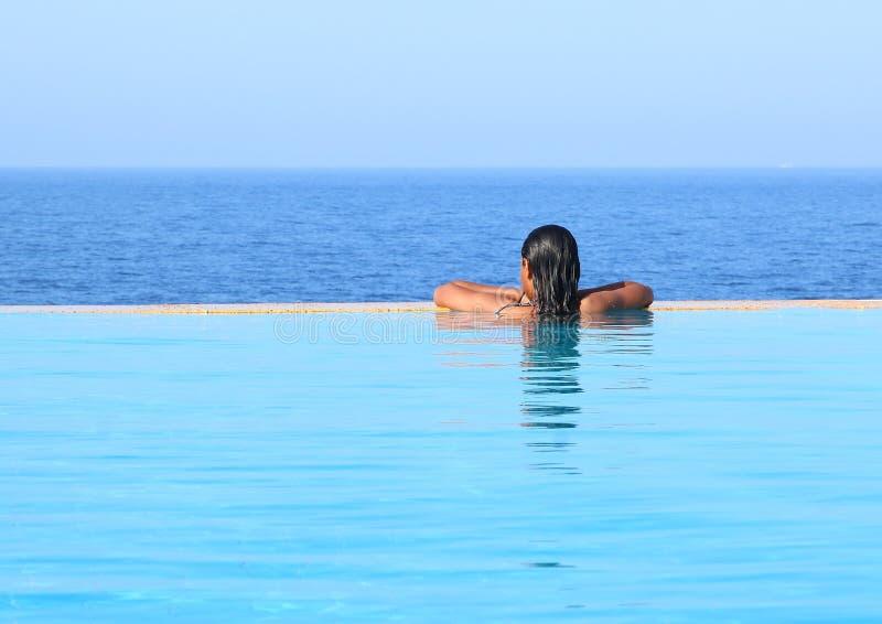 游泳场的年轻女人由海 免版税库存图片
