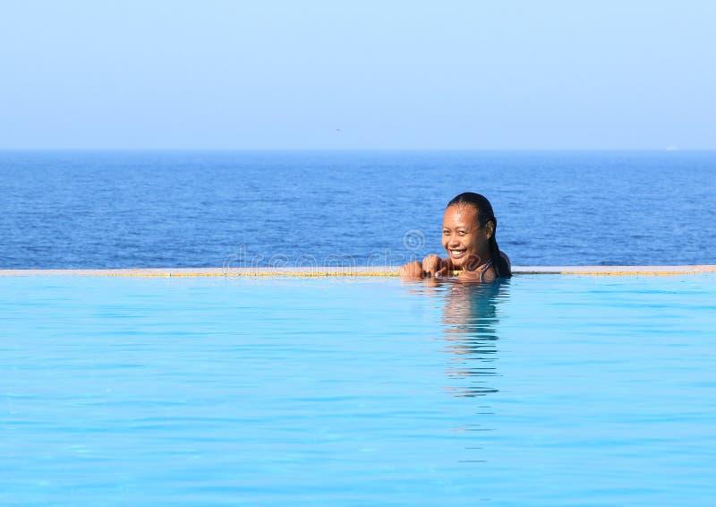 游泳场的微笑的热带女孩由海 库存照片