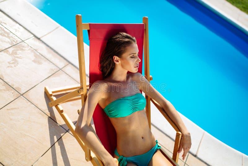 游泳异乎寻常的美丽的妇女晒日光浴和 免版税库存照片
