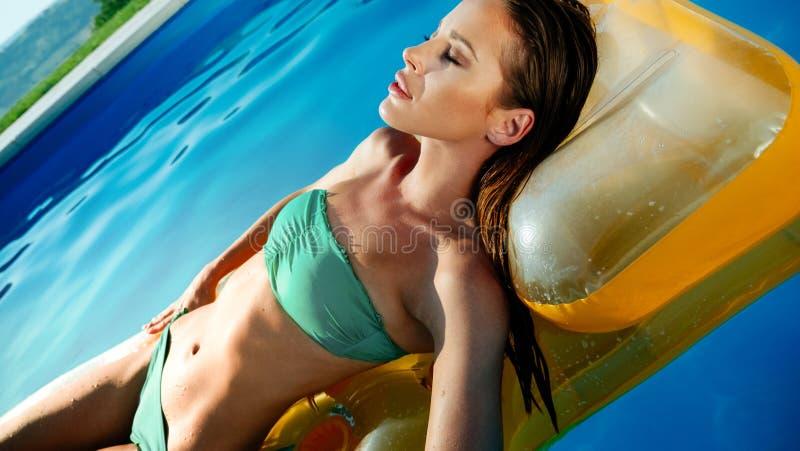 游泳异乎寻常的美丽的妇女晒日光浴和 免版税图库摄影