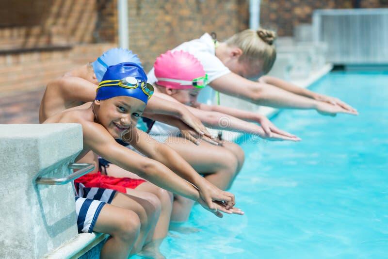 游泳教练员教的孩子在水池边 库存照片