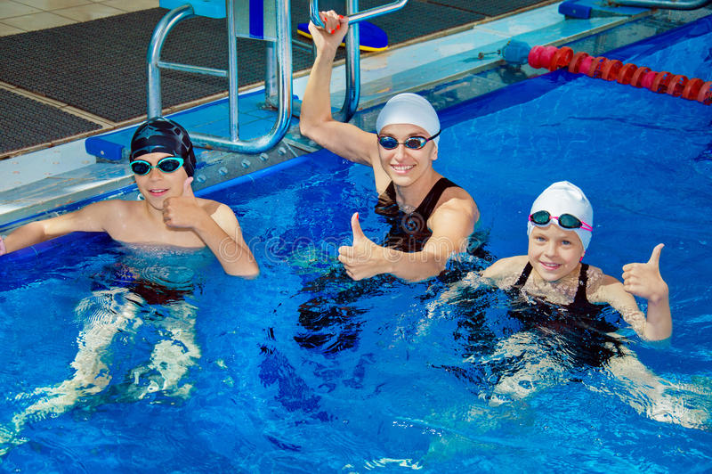 游泳教练显示孩子的锻炼 免版税库存图片