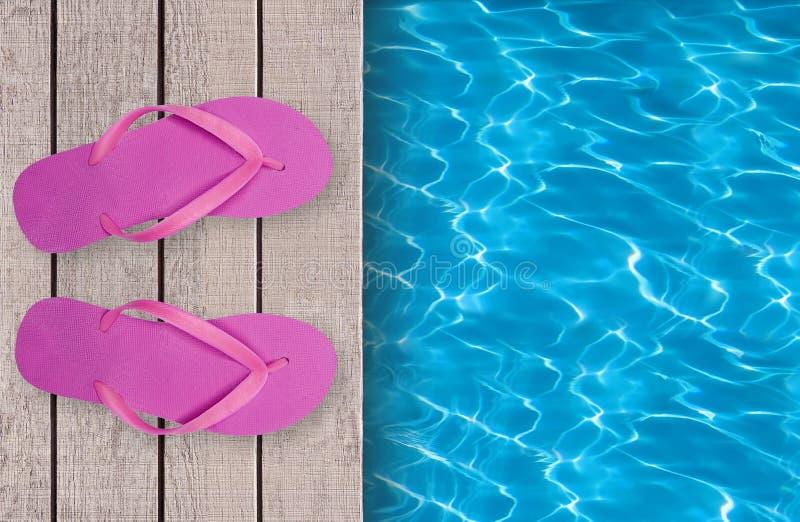 游泳池、木甲板和桃红色海滩鞋子 免版税库存照片