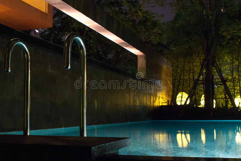 游泳池区域在与软性发光的室外照明设备的晚上在昂贵的家在有平坦的水和ro的热带东南亚 免版税库存图片