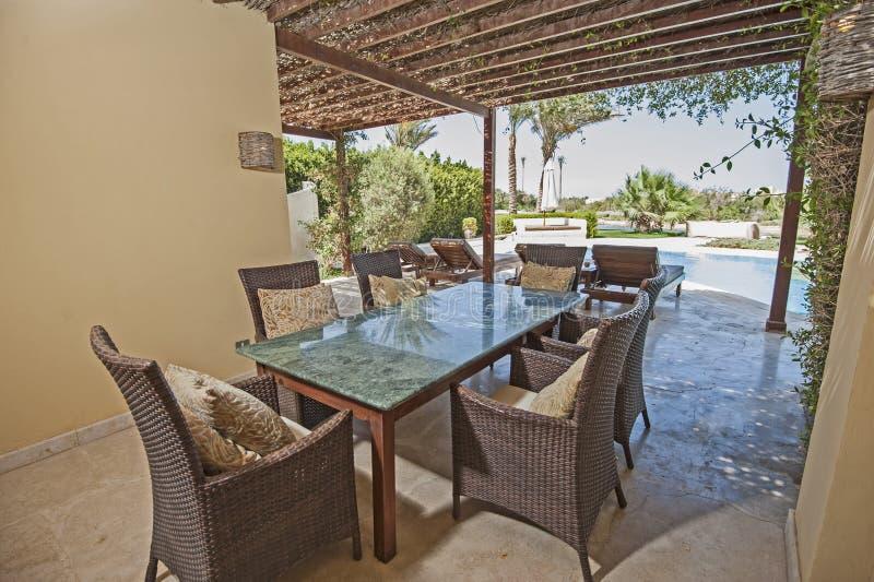 游泳池和室外饭厅在豪华热带holi 免版税库存照片