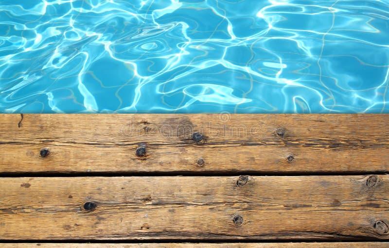 游泳池和木甲板背景顶视图  免版税库存照片