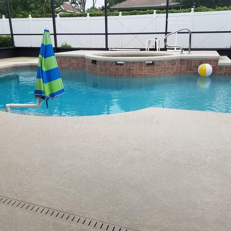 游泳池在有水池甲板和温泉极可意浴缸的屏幕封入物 免版税库存图片