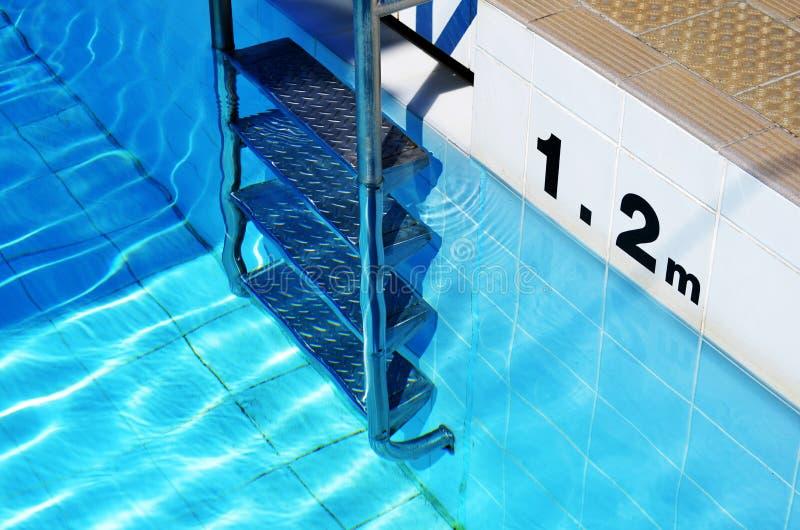 游泳池梯子和深度标志 免版税库存照片