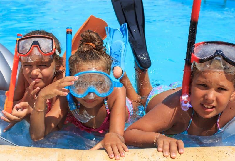 游泳池的三个女孩 库存照片