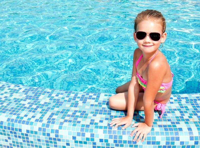 游泳池的可爱的微笑的小女孩 免版税库存照片