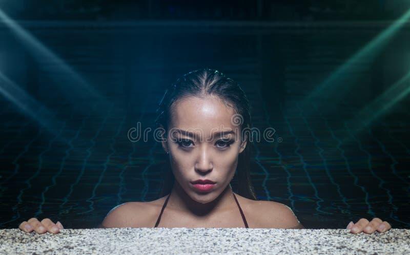 游泳池的性感的妇女在晚上时间 库存照片