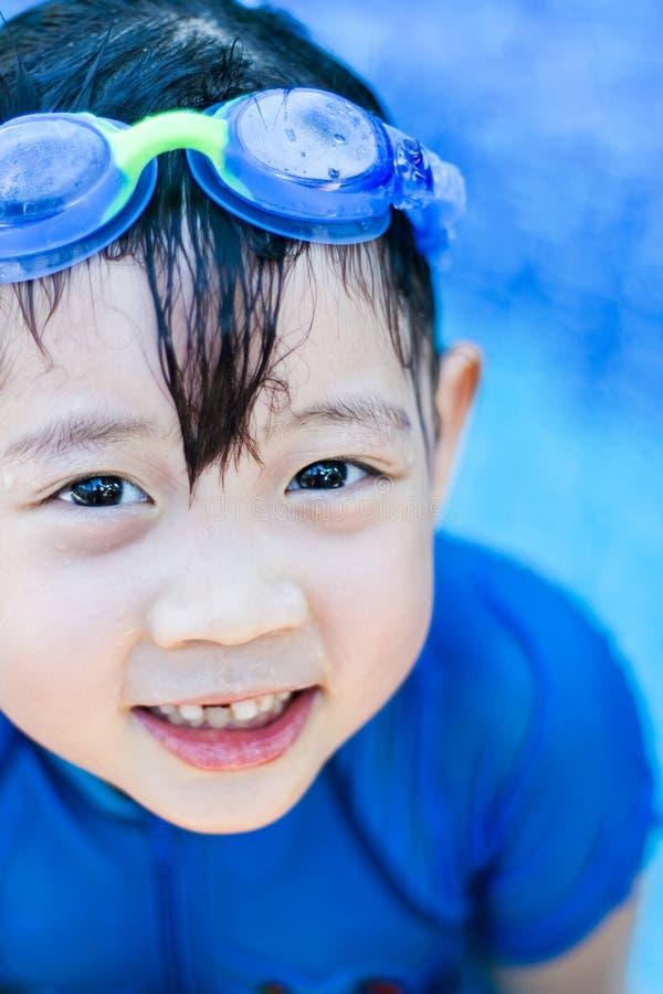 游泳池的逗人喜爱的亚裔女孩 免版税库存照片
