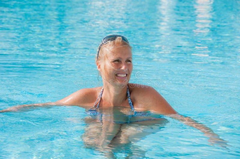 游泳池的年轻白肤金发的妇女 免版税库存图片