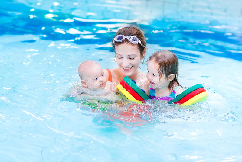 游泳池的年轻活跃母亲与两个孩子 免版税库存照片