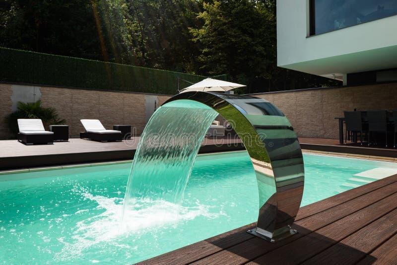 游泳池细节与喷泉的在现代别墅 免版税库存照片