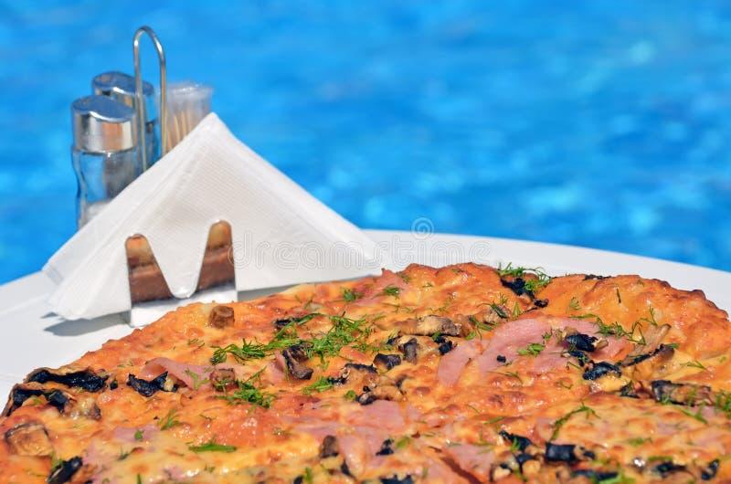 游泳池背景中美味的披萨 库存图片