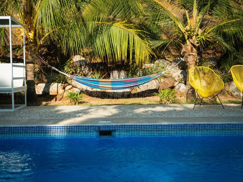 游泳池边、大海和吊床 免版税库存图片
