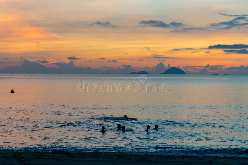 游泳的人在海在黎明 免版税库存图片