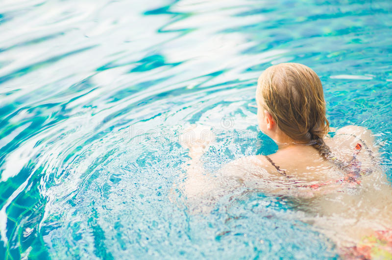 游泳的少妇开始在热带海滩胜地水池 免版税库存图片