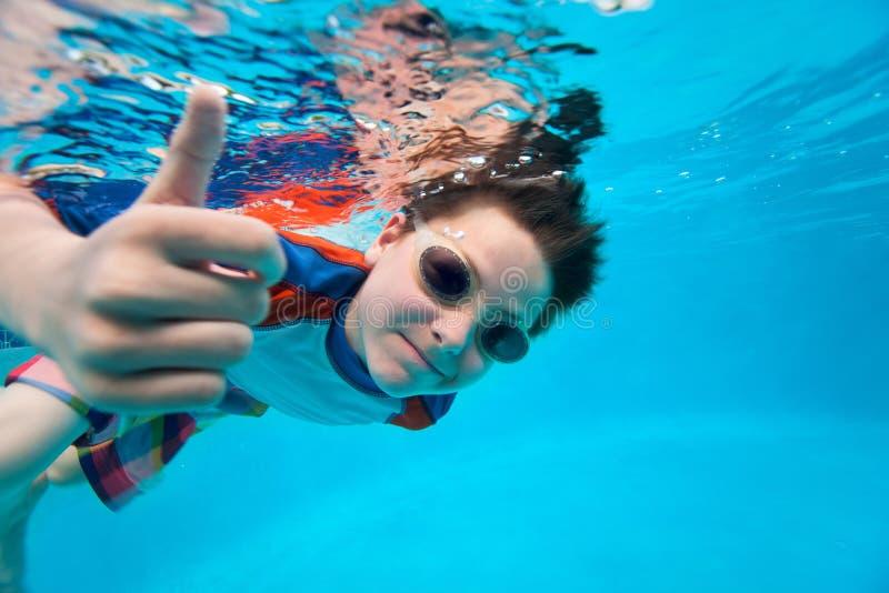 游泳的男孩在水面下 免版税库存照片