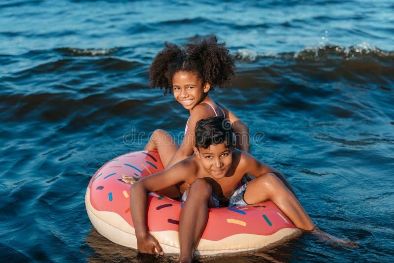 游泳的管的非裔美国人的兄弟姐妹 库存照片