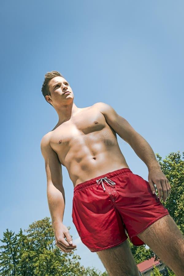 游泳短裤的年轻人 免版税库存图片