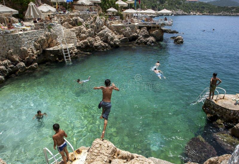 游泳者在土耳其地中海海岸的Kas喜欢跳进海在岩石海滩 图库摄影