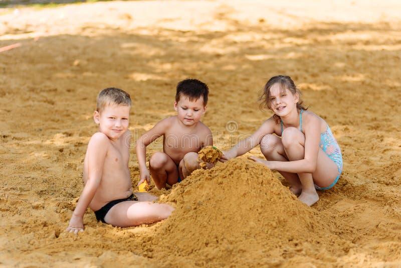 游泳衣的三个愉快的高加索孩子建造塔黄沙在海滩 免版税库存图片