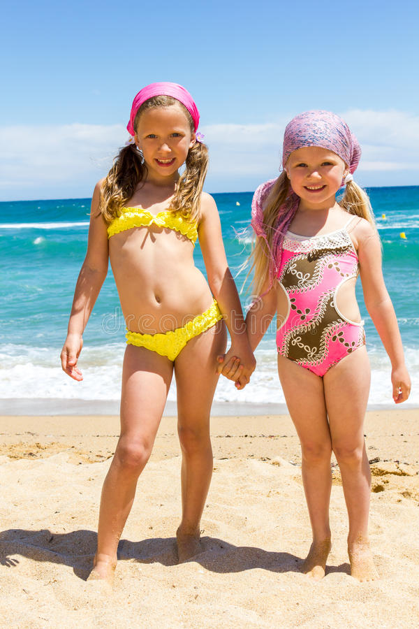游泳衣的两个女孩在海滩。 库存照片