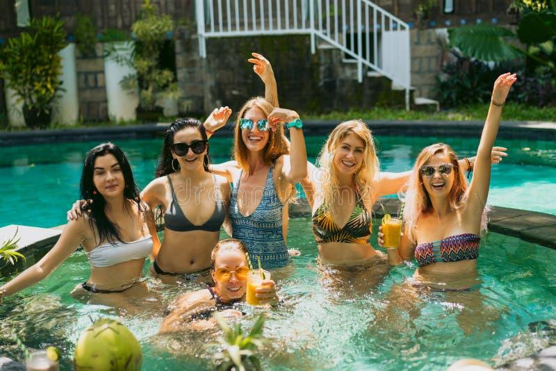 游泳衣的微笑对照相机的美丽的年轻女人和太阳镜,当获得乐趣一起在游泳时 库存图片