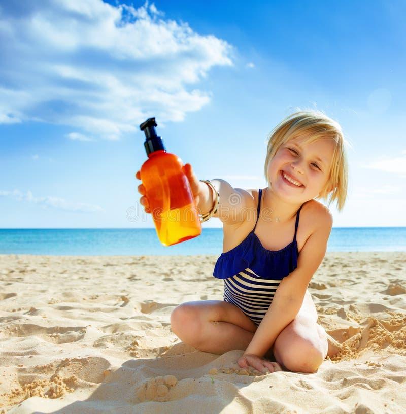 游泳衣的微笑的健康孩子在显示化妆水的海岸 库存照片