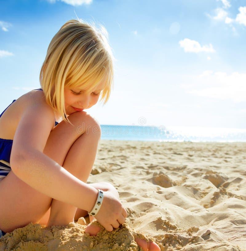 游泳衣的愉快的白肤金发的女孩在海滩使用 免版税库存照片