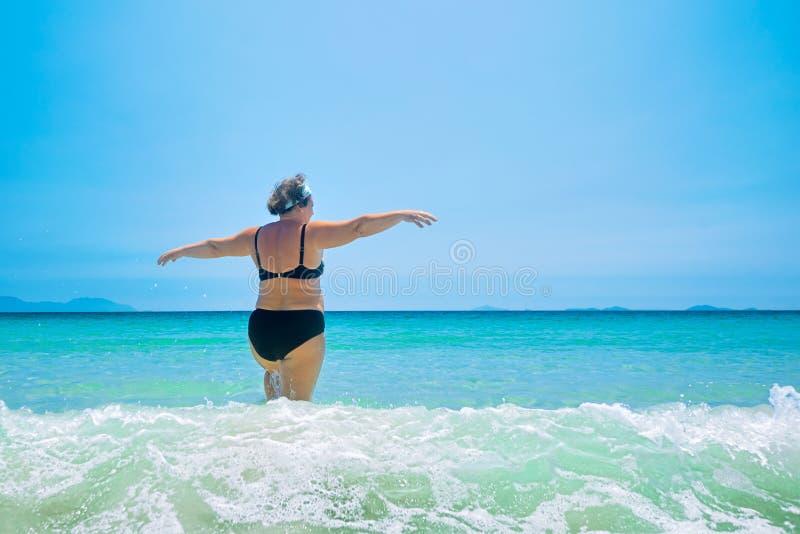 游泳衣的成熟妇女在海 免版税图库摄影