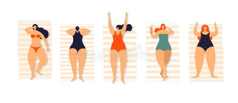 游泳衣的晒日光浴的年轻美女在毛巾说谎 库存照片
