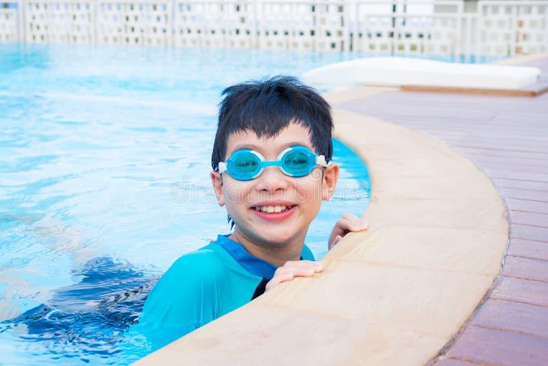 游泳衣的男孩微笑在游泳池的 免版税库存图片