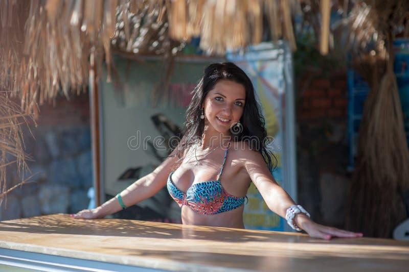 游泳衣的美丽的深色的女孩在酒吧 免版税图库摄影