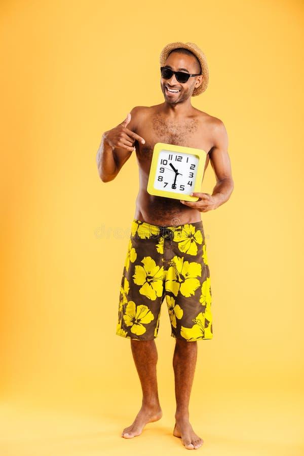 游泳衣的美国黑人的人把手指指向的壁钟 免版税库存照片