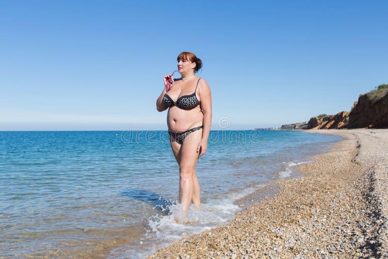 游泳衣的超重妇女走沿海滨的 库存图片