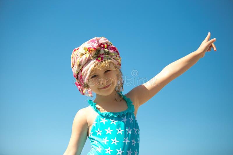游泳衣的逗人喜爱的小女孩反对蓝天 免版税库存图片