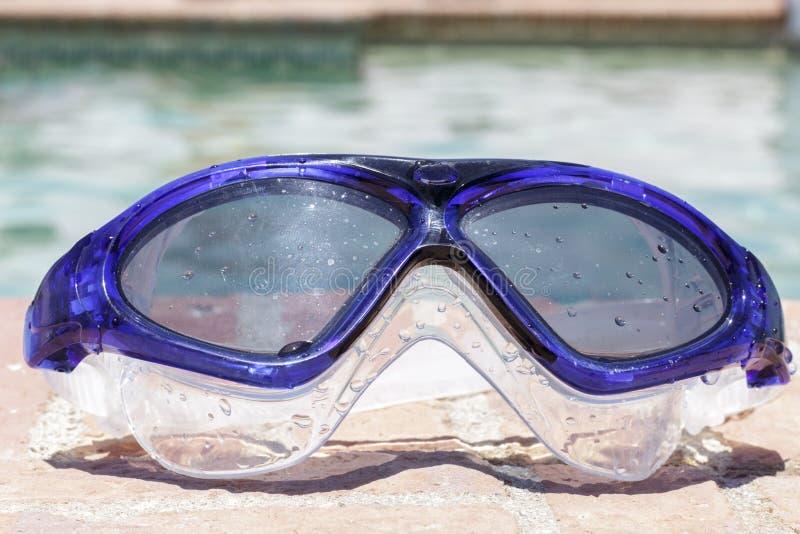 游泳风镜在游泳池的边缘 库存图片