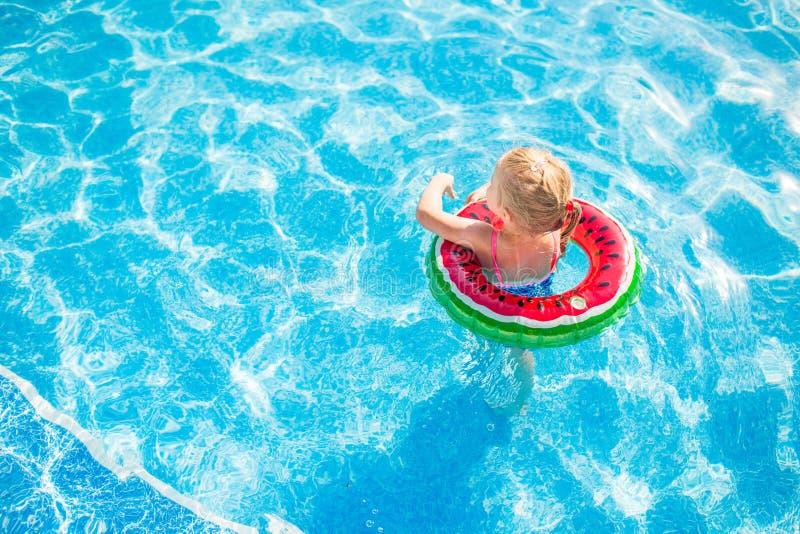 游泳,暑假-使用在大海的可爱的微笑的女孩用lifebuoy西瓜 库存照片