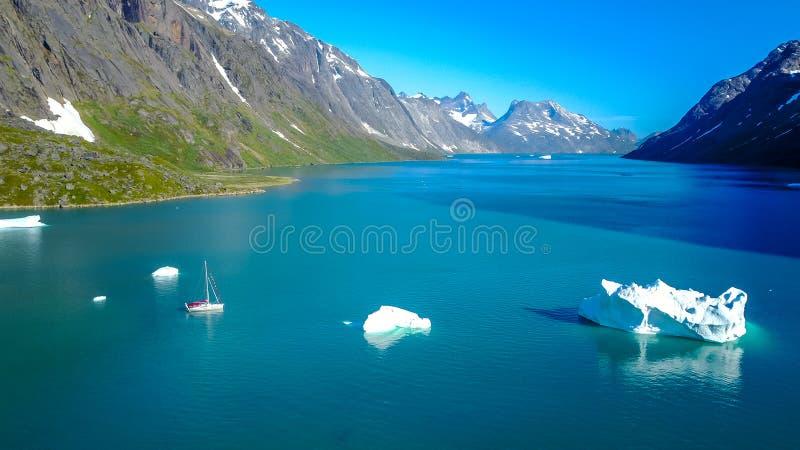 游艇和冰山 令人惊讶的aerophoto 格陵兰自然海湾 库存图片
